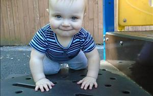 Physical development skills are critical to infants. Arlo is having fun gaining more muscles while playing outside!