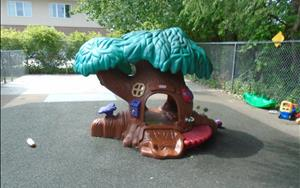 One of the favorite parts of the Toddler playground is the treehouse.  The treehouse is a great way to help the toddler build their large motor skills as well as an area for them to use their imagination.  The toddlers enjoy sitting on the small benches on the outside of the treehouse or climbing up the small ramp that leads inside and going down the small slide.