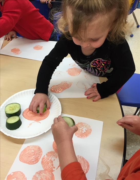 Toddlers painting with cucumbers