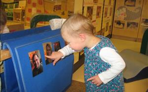 "One of the themes in our Infant Classroom is ""Friends and Family."" Family members were encouraged to provide pictures of themselves to place in the classroom. Children worked on developing their language skills by naming different family members."
