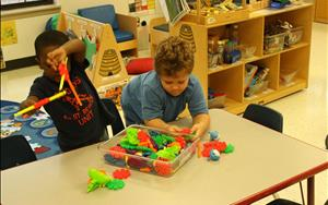 Children learning through play during small-group learning time with manipulatives.
