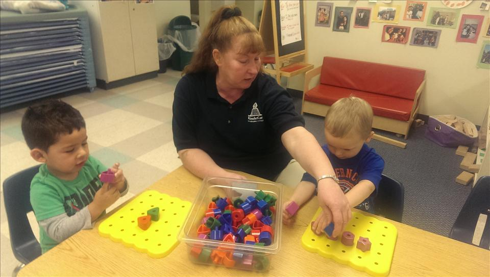 Ms. Annette playing with the peg boards with the children.