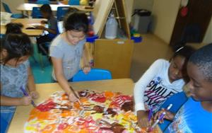 School age students creating a fall handprint tree.