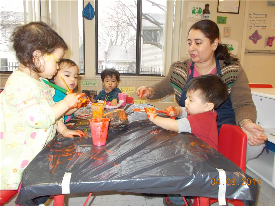 The toddlers enjoy exploring with different paint colors.