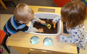 Two of our Discovery Preschoolers exploring the wonders of dirt! This activity is not only fun--it is teaching them about different textures as well as social interaction skills.