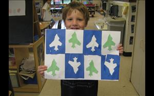 One of the School Age children shows off one of his many art pieces he made during the art theme.
