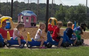 Discovery Preschoolers (Two's) making a bike train on the playground