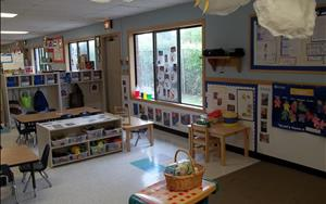 A different view of the toddler classroom.  The large tables are also used as an area for the children to participate in large and small group activites, art projects as well as playing with the various bucket toys and puzzles.  The toddlers also have access to a sensory table that is filled with something new each month that reflects on what they are learning.