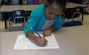 She is learning to associate sounds with letters as she traces the letter Uu.