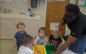 Mobile infants showing social and emotional development by beginning to interact with other children, smiling, and vocalizing while playing in the water with Ms. Vicky.