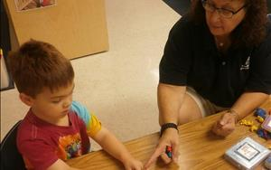 In our preschool classroom, Ms. Laura Ann is working with Jett on color recognition.