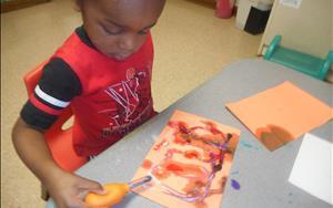 A student in our Discovery Preschool Classrooms uses an eye dropper to see what happens when he places food coloring on his salt art.