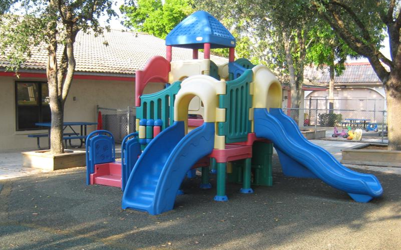 The preschool playground is equipped with riding toys, age appropriate play equipment, basketball hoop and rubberized matting for safety. Beautiful trees naturally shade this high energy fun space.