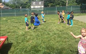 The Pre-K class enjoying a game of beach volleyball outside.