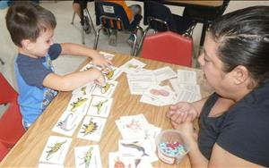 "Ms. Laurie is working with 4 year old Kayden in identifying and learning about dinosaurs during our ""Dinosaur"" theme."