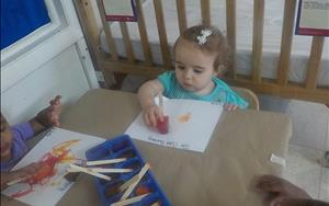 Infants painting with popsicles