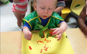Our toddlers bring the outside in as they paint with leaves and twigs.