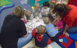 The toddlers are working on their social and emotional development in a simple art activity.