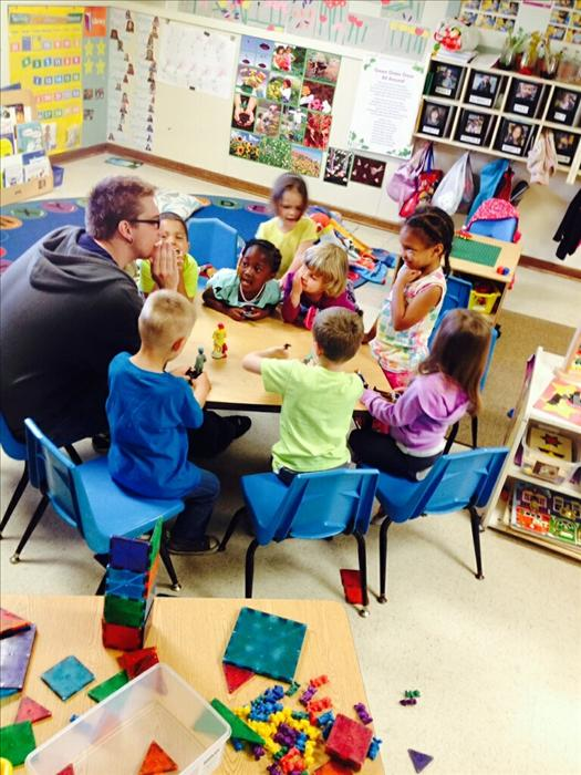 One of our preschool teachers is playing with students in one of our Preschool Classrooms during center time.