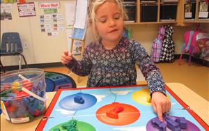 We use a variety of techniques and materials to make sure that children are always learning. This child is building her cognitive ability by playing a color matching game.