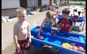 Several Preschoolers enjoy the water table during one of our many water days.