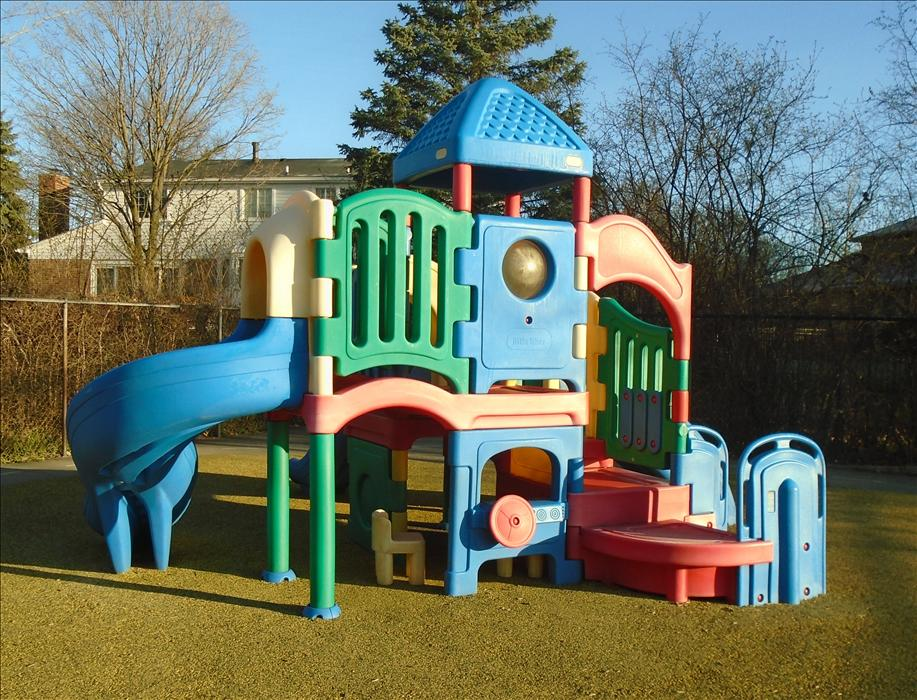 The children enjoy climbing in the play structure, racing around on bikes, and exploring in the sandbox.
