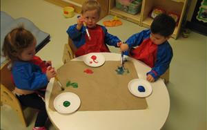 Painting is just one of the many ways that our infants are able to creatively express themselves. These three children are working together to create a classroom mural.