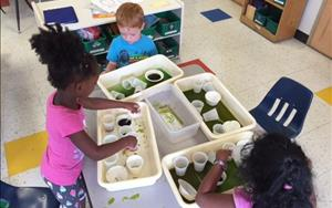 Children exploring with water and seeing what happens when you mix different colors together.