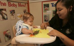 Ms. Ada helps baby Emerson with his very first painting project.