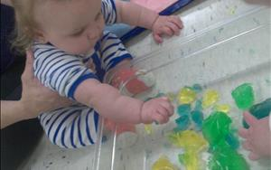 This little one is enjoying squishing, mixing, and holding multicolored gelatin during one of our Wet and Messy activities. Sensory activities teach infants important information about the world around them and fosters healthy brain and language development as teachers talk with the babies and encourage exploration!