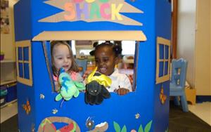Hailey and Sarai putting on a puppet show in dramatic play.