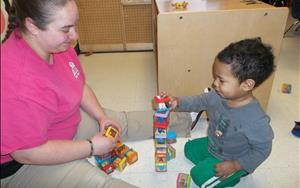 Stacking blocks with his teacher.