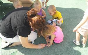 Toddlers are doing hand and foot tracing on the playground.