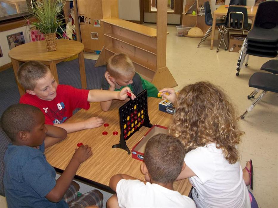 School Age Classroom - students playing a game of checkers