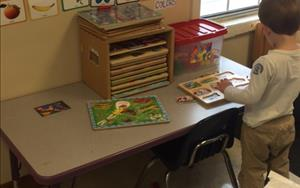 In our Preschool math area a child has fun putting together a puzzle