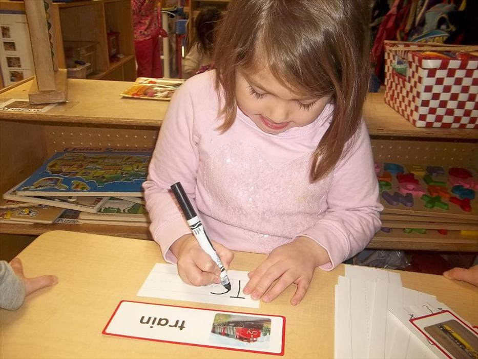 Prekindergarten student writes a word wall word for theme