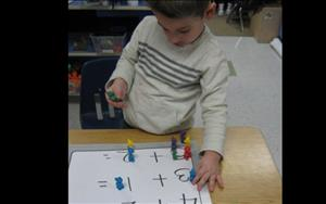 "A good portion of our Preschool curriculum focuses on small math concepts. Here our Preschool classroom was identifying numbers while working on one to one correspondence. The children were encouraged to identify each number and utilize our ""Kelsey Counters"" to add the numbers up and then count the total number of ""Kelsey Counters."""