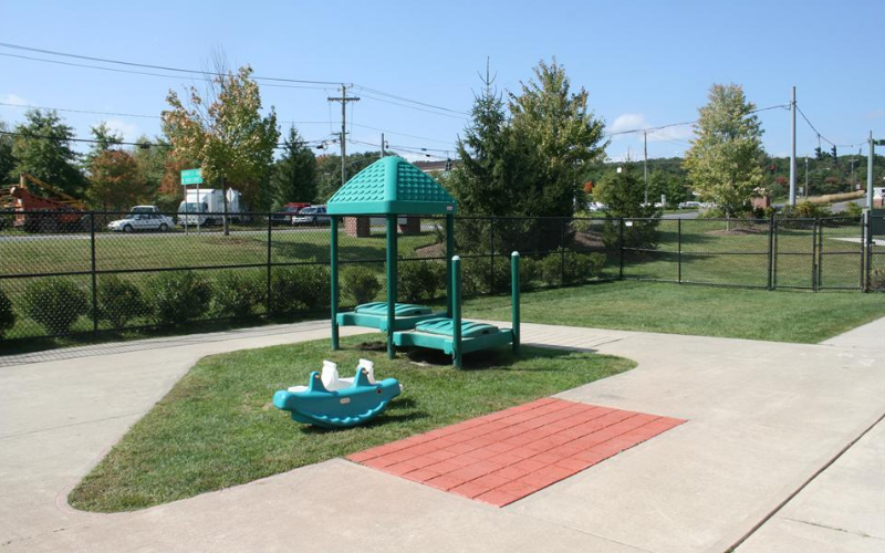 This playground is utilize by our Discovery Preschool Program. On this playground you will find ample grass space to run, tricycles with a bike path, a sandbox, sensory activities, multiple play houses and plenty of toys for the children to take out and play.