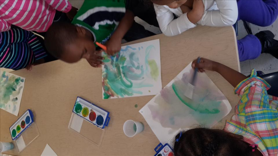 Preschool classroom exploring water color by painting small individual pictures.