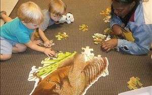 "Ms. Brenda on the floor with Evan and Tanner helping them with the dinosaur floor puzzle during our ""Dinosaurs"" theme."