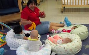 Ms. Yolanda assists our infant learners in the beginning stages of language and literacy by reading a story.