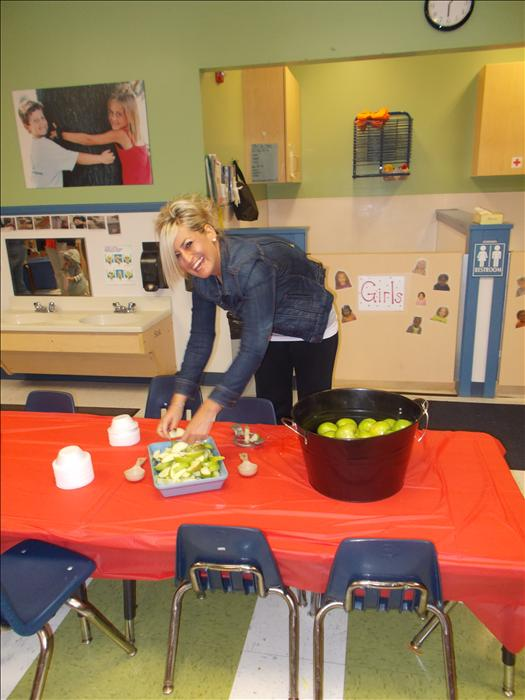Preschool Teacher Ms. Angel running the Carmel Apple Dipping Station