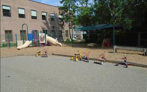 This is our large Preschool Playground! Our Preschool, Jr. K, and Pre-K students love getting some energy out in our large outdoor playground! There is a large concrete area for bike riding, chalk and other fun activities, as well as a large structure for climbing and sliding! A large tent covers an area of the playground to provide some shade while the teachers and students take their curriculum outdoors!