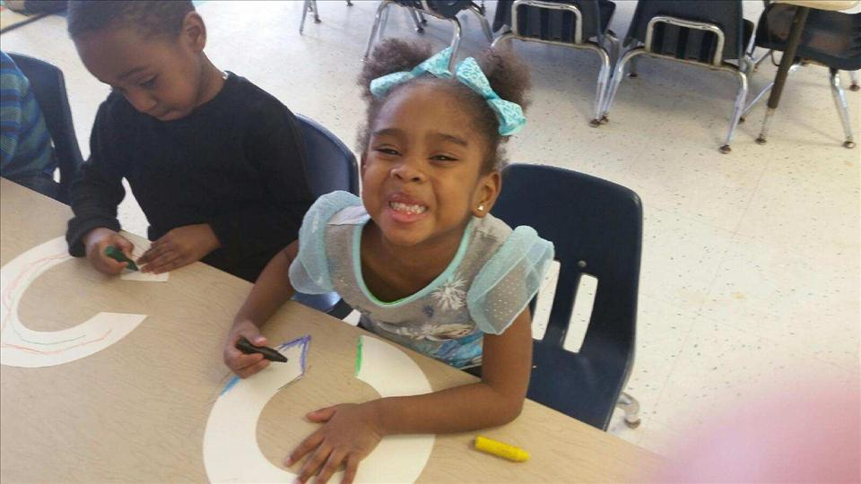 Preschool student being silly while working on her letter collage.