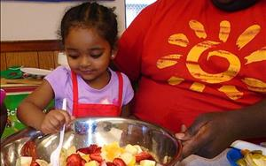 The Discovery Preschool class (2s) get to learn through fun cooking projects. Counting the fruit helps teach math for kids.