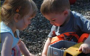 Two toddlers enjoy the Discovery Preschool playground and a little sun.