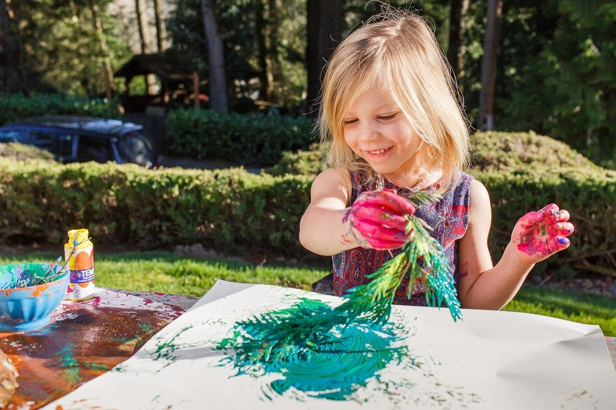 girl happily painting with a leafy tree branch