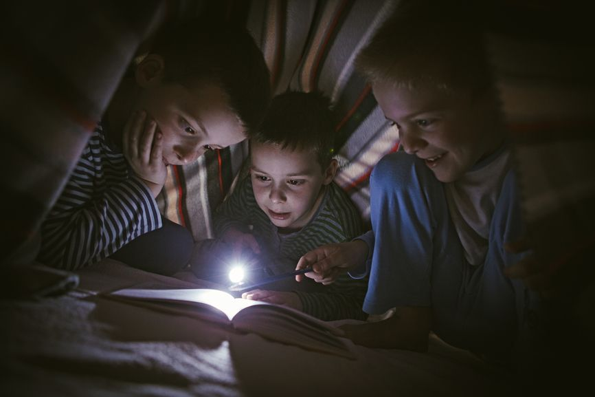 three boys reading under blanket with flashlight