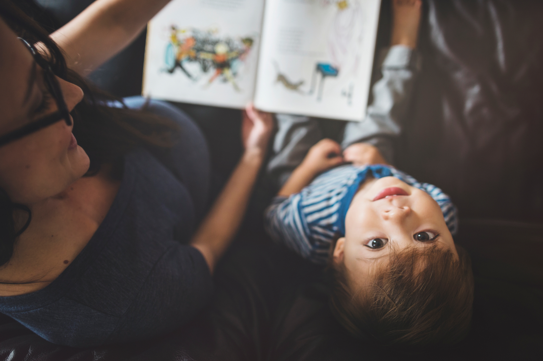 mom reading to boy as he looks up at camera Stocksy / 347620