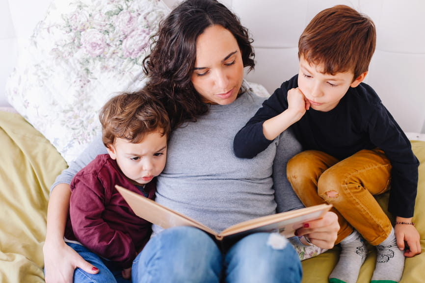 Mom and two boys reading